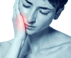 woman has a toothache in the upper row of teeth