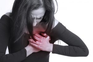 A woman hold her breast because of pain, white and black picture with red.